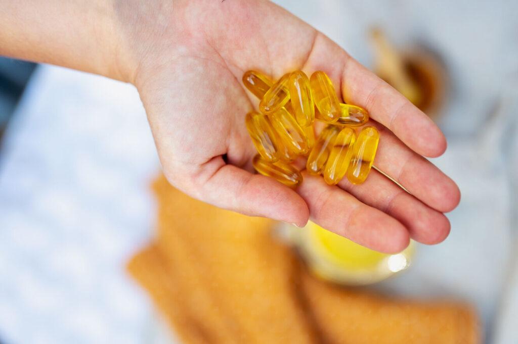 Eine ausgestreckte Hand mit Vitamin D Kapseln