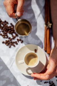 Hand hält eine Kaffeetasse, die auf dem Tisch steht